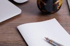 Weißbuch und Stift auf Tabelle lizenzfreie stockbilder