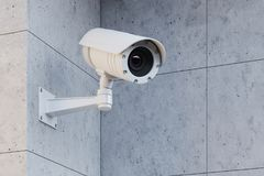 Weiße Überwachungskamera auf einer grauen Wand lizenzfreie abbildung