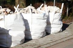 Weiße Abfalltaschen mit Schuttsteinen Stockfotografie