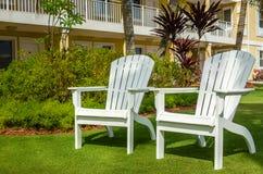 Weiße Adirondack-Stühle in einem Garten Lizenzfreies Stockfoto
