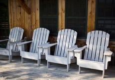 Weiße Adirondack-Stühle in Folge Stockfotos