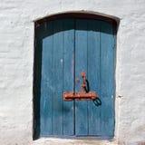 Weiße alte Backsteinmauer mit verwitterter Tür oder Tor Lizenzfreie Stockfotos