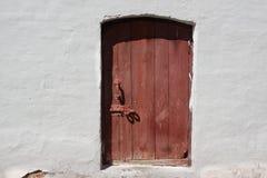 Weiße alte Backsteinmauer mit verwitterter Tür oder Tor Stockfotografie