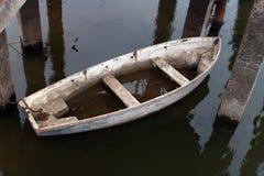 Weiße alte undichte Bootshälfte im Wasser auf dem Fluss stockfoto