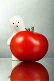Weiße Andenkenfigürchen mit roter Tomate Stockfoto
