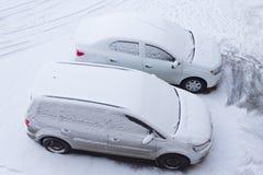 Weiße Autos im Parkplatz morgens nach Schneefälle Stockbilder