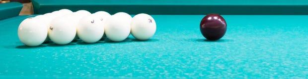 Weiße Bälle für großes Billard liegen auf einem grünen Stoff, ein langes Foto stockfotografie