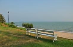 Weiße Bänke auf dem Strand vor dem Meer Stockfotografie
