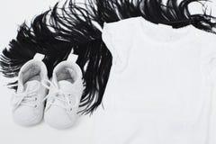 Weiße Baby-Kleidung auf schwarzer Feder Lizenzfreie Stockbilder