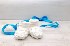 Weiße Babyschuhe mit blauen Jungesternen und blaues Band auf dem Ba Lizenzfreie Stockfotos