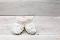 Weiße Babyschuhe mit blauen kleinen Sternen auf einem hölzernen Hintergrund Stockbild