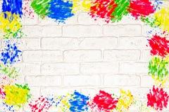 Weiße Backsteinmauer mit buntem Feld Stockfotografie