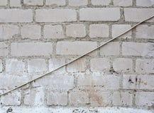 Weiße Backsteinmauer mit dem Hängen des elektrischen Kabels Lizenzfreies Stockbild