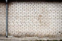 Weiße Backsteinmauer mit einem Regenrohr Stockfotos