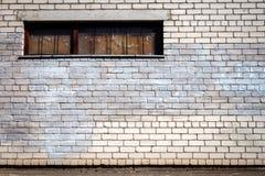 Weiße Backsteinmauer mit einem verschalten Fenster Stockbild