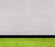 Weiße Backsteinmauer mit schwarzem horizontalem nahtlosem Muster und Rasen Lizenzfreie Stockbilder