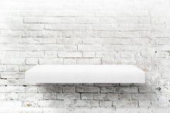 Weiße Backsteinmauer und Regal lizenzfreie stockfotos