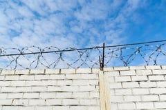 Weiße Backsteinmauer und Stacheldraht Lizenzfreie Stockfotos
