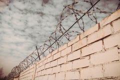 Weiße Backsteinmauer und Stacheldraht Stockfotografie