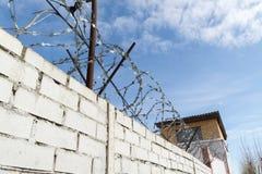 Weiße Backsteinmauer und Stacheldraht Lizenzfreie Stockbilder