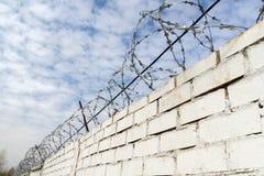 Weiße Backsteinmauer und Stacheldraht Stockfotos