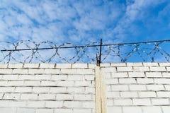 Weiße Backsteinmauer und Stacheldraht Stockfoto