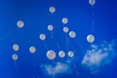 Weiße Ballone auf dem blauen Himmel Stockfotos