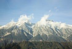 Weiße Bergspitzen in den Wolken stockbild