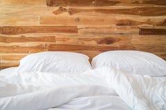 Weiße Bettwäscheblätter und Kissen, unordentliches Bettkonzept Stockfoto