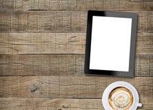 Weiße Bildschirmanzeige und Kaffee des Tablets auf altem hölzernem Hintergrund Lizenzfreies Stockfoto