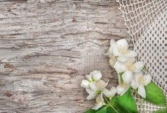 Weiße Blumen auf Spitzegewebe und altem Holz Stockfoto