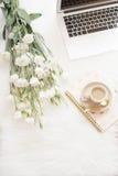 Weiße Blumen des Laptops, des Kaffees, des Notizbuches und eines großen Blumenstraußes auf dem Boden auf einem weißen Pelzteppich Stockbild