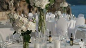 Weiße Blumen im Vase werden auf Tabellen zu einer Feier durch Meer eingestellt stock video footage