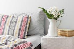 Weiße Blumen und Bücher auf einem Nachttisch Stockfotografie
