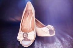 Weiße Brautschuhe mit Knoten und Diamanten auf ledernem Sofa lizenzfreies stockbild