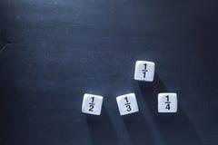 Weiße Bruchmathezahl würfelt auf Tafel Stockfoto