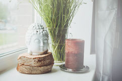Weiße Buddha-Kopffigürchen auf hölzernem Stand mit großer brauner Kerze ein Fensterbrett, grüner Blumenbetriebshintergrund Haus Stockfoto