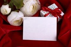 Weiße Butterblume blüht grüne Geschenkbox des Ranunculus mit rotem Band auf roter Gewebehintergrundkarte für Text Kopieren Sie Pl Lizenzfreie Stockfotos