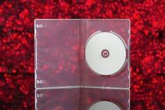 Weiße CD in der Klarsichtschachtel mit rotem Hintergrund Lizenzfreie Stockfotografie