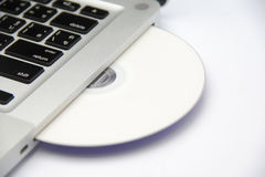 Weiße Cd- oder dvdplatte im Laptop Lizenzfreie Stockbilder