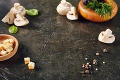Weiße Champignon-Pilze auf dunklem Steinplatten-Hintergrund mit D Stockfotografie