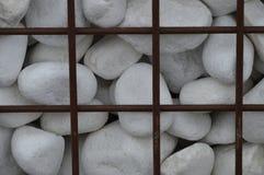Weiße Dekorationsfelsen hinter einem Eisenzaun Lizenzfreies Stockfoto