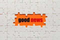 Weiße Details des Puzzlespiels auf orange guten Nachrichten des Hintergrundes und des Wortes stockfotos