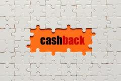 Weiße Details des Puzzlespiels auf orange Hintergrund und Wort Cashback lizenzfreie stockfotos