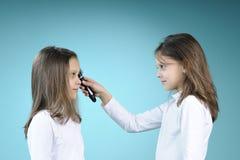 weiße Doppelmädchen, die Haar auftragen stockbilder
