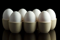 Weiße Eier in den Eierbechern auf Schwarzem Lizenzfreie Stockfotografie