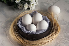 Weiße Eier in der hölzernen Schüssel auf weißem Hintergrund, selektives focuse Stockbilder