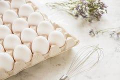 Weiße Eier in einem Kasten auf einem hellen Hintergrund Stockbild