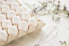 Weiße Eier in einem Kasten auf einem hellen Hintergrund Stockbilder