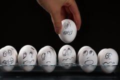 Weiße Eier mit Bedrängnisgesichtern Stockbild